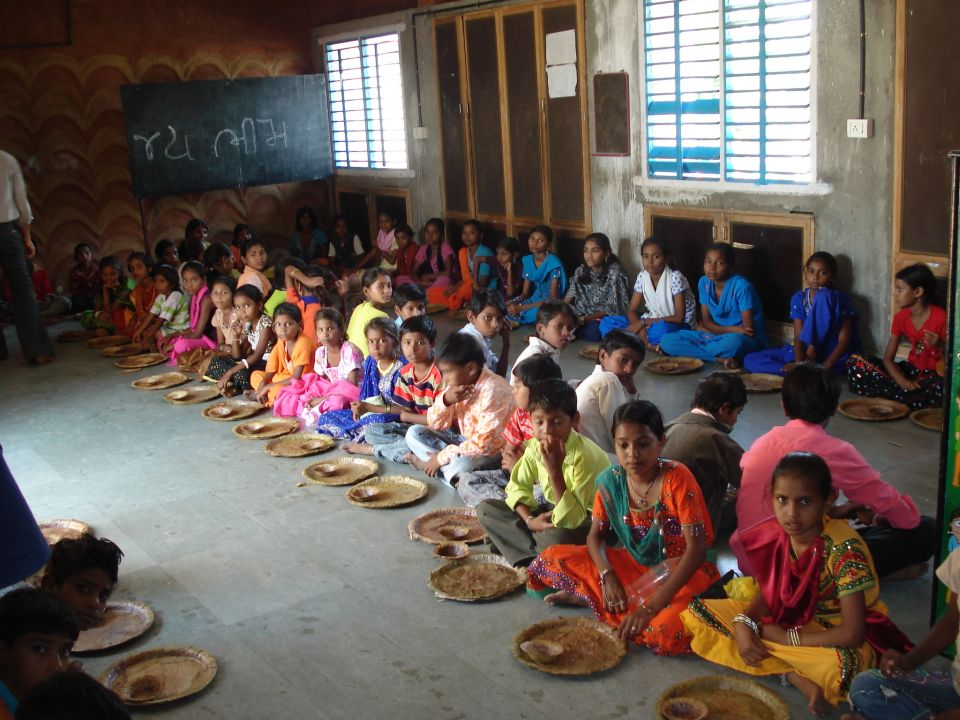 A photo of students being served midday meal in school