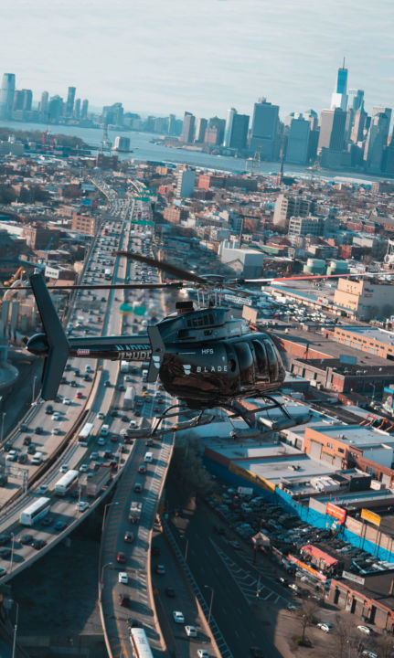 A photo of a Blade helicopter with the Manhattan skyline visible in the background