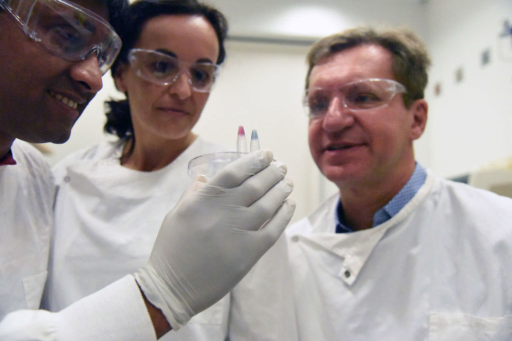 Dr Abu Sina, Dr Laura Carrascosa, and Professor Matt Trau with the two test tubes testing for cancer. Pink reflects positive for cancer, and blue reflects negative.