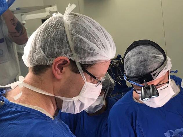 A photo of two doctors performing the transplant