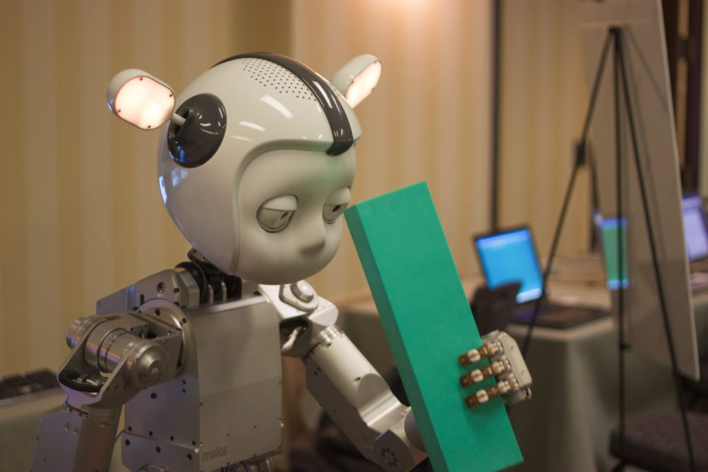 A photo of humanoid robot playing with blocks