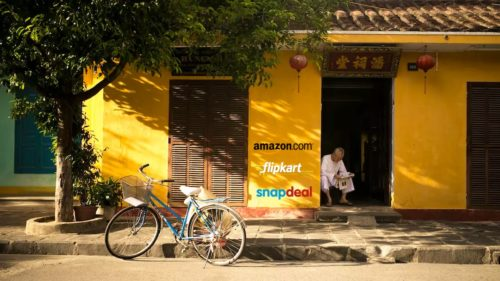 A photo of a man sitting in the doorway, reading a newspaper, as the wall next to him has Amazon.com, Flipkart.com and SnapDeal painted on it