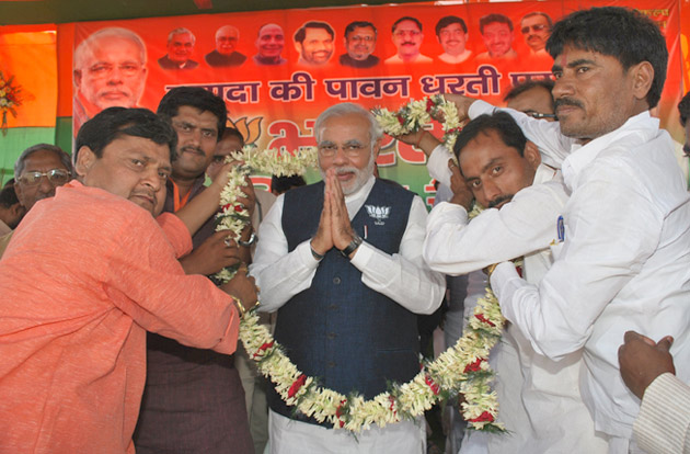 Photo of Modi being offered a garland at a rally