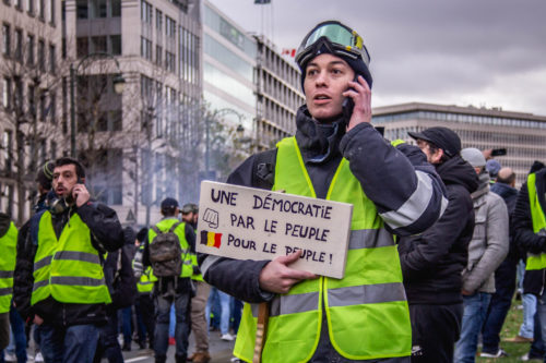 """Photo of a gilets jaunes protestor holding a placard that reads """"One Democaracy for the people, by the people"""" in French."""