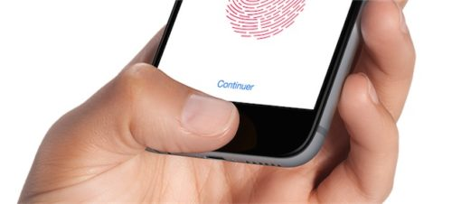 A photo of a a disembodied hand setting up Touch ID on an iPhone