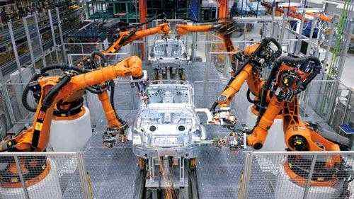 A photo of robotic arms in a car factory assembling the car chassis.