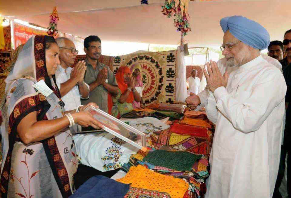 Manmohan Singh greets villagers at a NREGA site in Rajasthan.