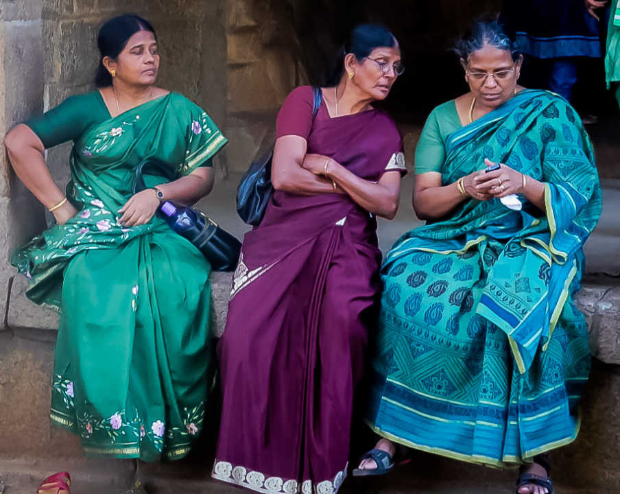 Three women looking at a cell phone.