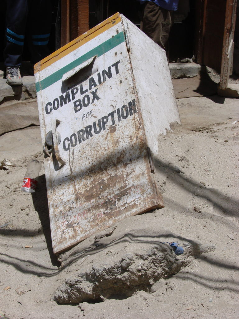 A complaint box against corruption burried in sand.